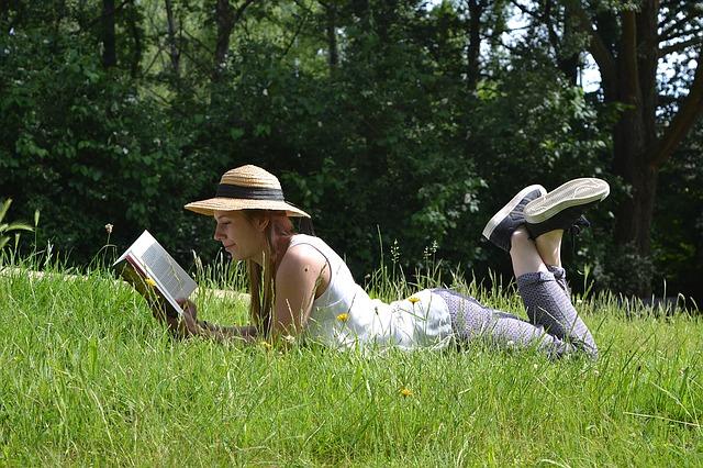 žena v trávě s knihou