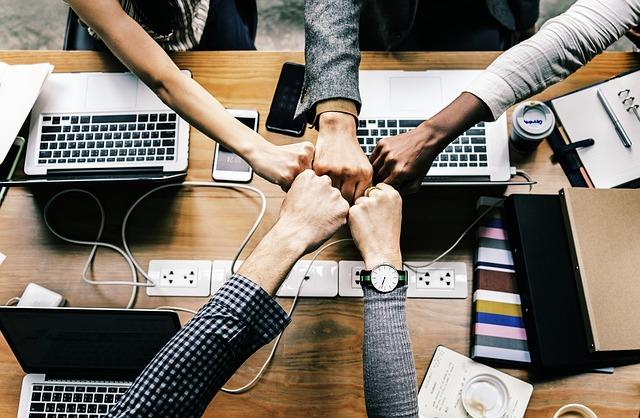 tým lidí, kteří spolu spolupracují – výraz spojených pěstí nad stolem jako základ úspěchu