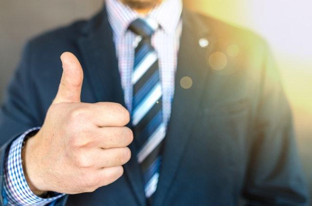podnikatel stojí v modré kostičkované košili a ukazuje palec nahoru.jpg