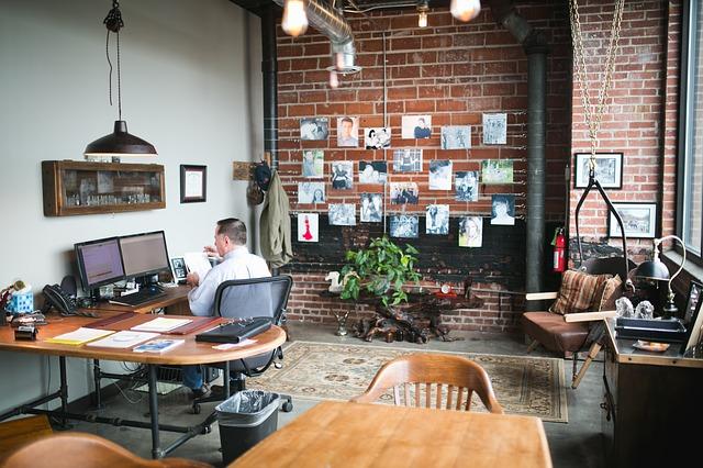 Kanceláře se zděnou zdí, mnoho obrázků, stůl, počítače a muž co pracuje
