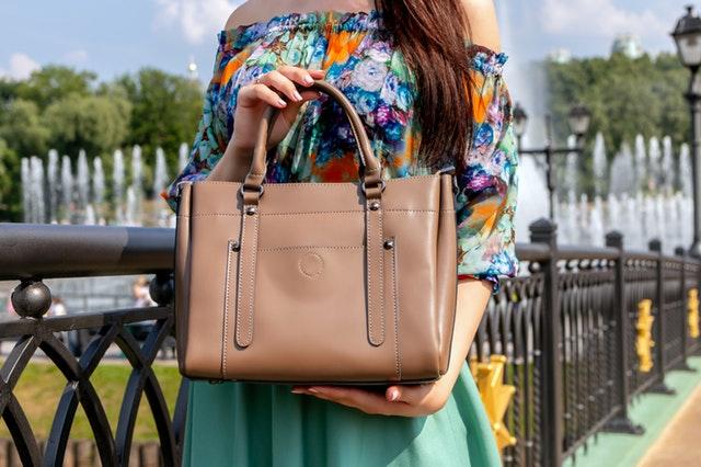 žena s pastelově hnědou kabelkou středního rozměru
