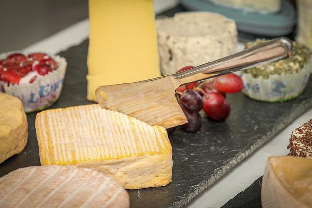 Různé druhy sýrů, položené na dřevěném prkénku